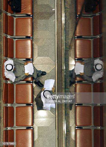 A Kuwaiti trader is reflected in a mirroras he sits inside the Kuwait's Stock Exchange hall after the end of the trading in Kuwait City on December...