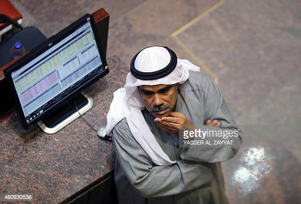 A Kuwaiti traders follows the stock market at the Kuwaiti Stock Exchange in Kuwait City on December 31 2014 Stock markets in the energyrich Gulf...