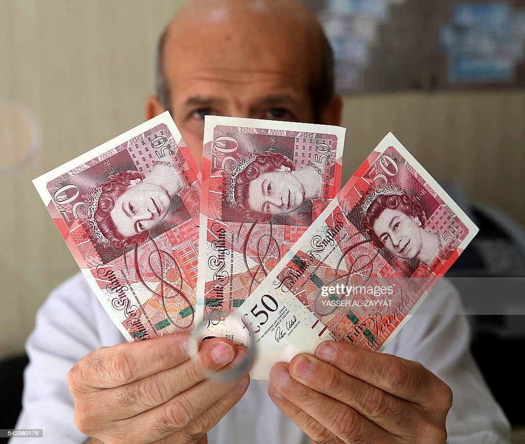 A Kuwaiti vendor holds British Pound banknotes at a money exchange shop in Kuwait City on June 25, 2016. The British Pound has plunged to its lowest rate since 1985 after the United Kingdom's vote to exit from the European Union. / AFP / YASSER