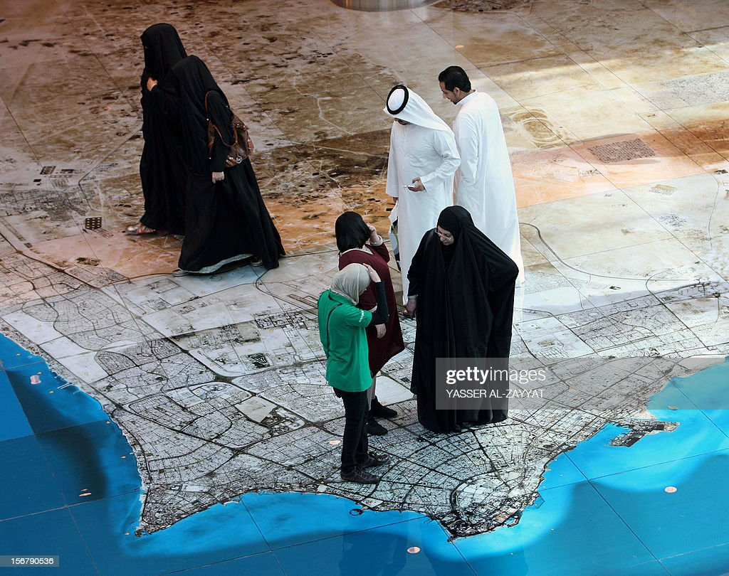 Kuwaitis look down at a large satellite image of Kuwait's map printed on the ground inside the Gulf emirate's Avenues Mall in Kuwait City on November 21,2012.