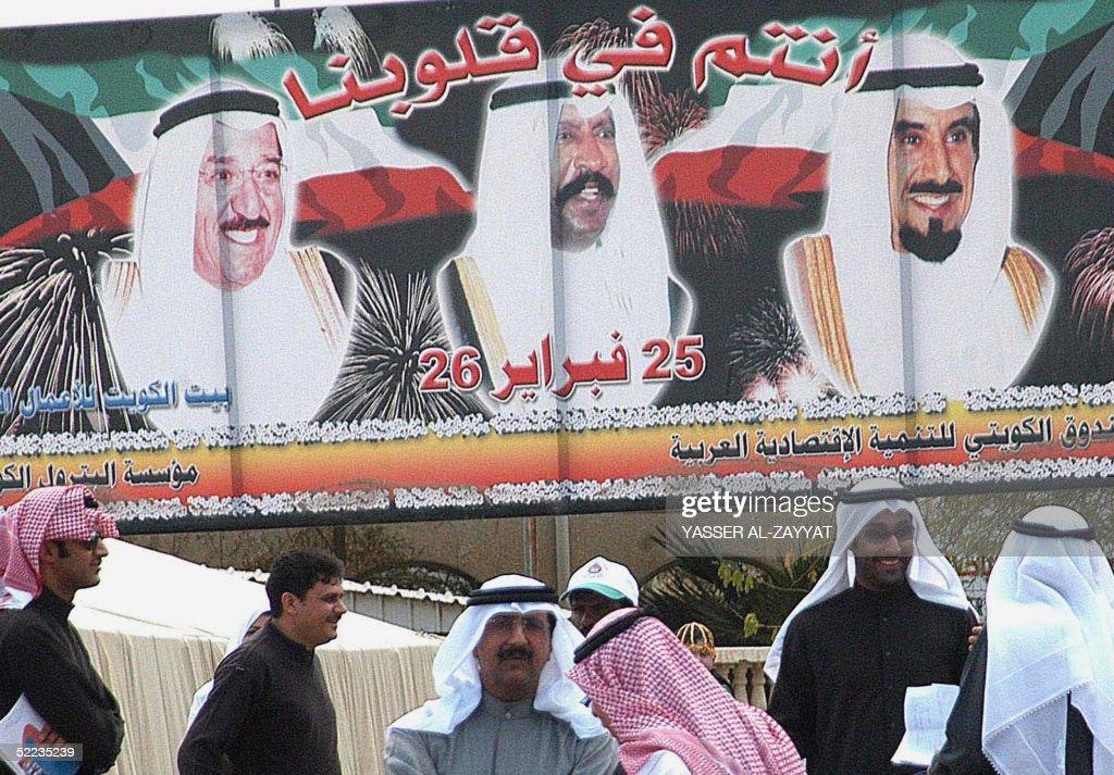 Kuwaitis stand 24 February 2005 under a huge billboard with photos of the Emir of Kuwait Sheikh Jaber alAhmad alSabah Crown Prince Sheikh Saad...