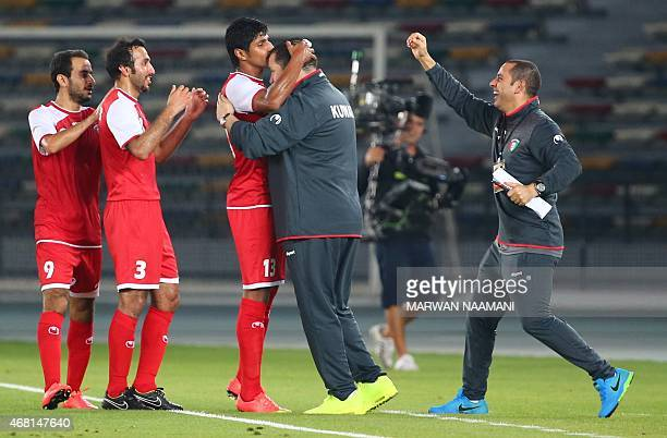 Kuwait's Musaed alEnazi kisses the head of his coach Nabil Maaloul after scoring a goal during their friendly football match against Colombia at the...