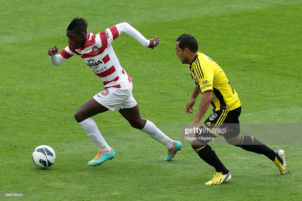 Kwabena Appiah Kubi of the Wanderers runs the ball past Leo Bertos of the Phoenix during the round 16 A-League match between the Wellington Phoenix and the Western Sydney Wanderers at Westpac Stadium on January 13, 2013 in Wellington, New Zealand.