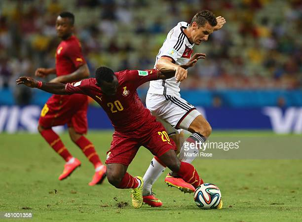 Kwadwo Asamoah of Ghana and Miroslav Klose of Germany compete for the ball during the 2014 FIFA World Cup Brazil Group G match between Germany and...