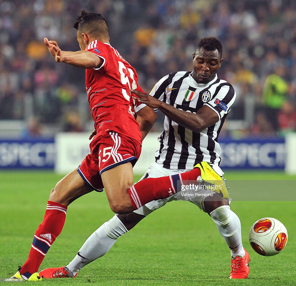 Kwadwo Asamoah (R) of Juventus clashes with Corentin Tolisso of Olympique Lyonnais durig the UEFA Europa League quarter final match between Juventus and Olympique Lyonnais at Juventus Arena on April 10, 2014 in Turin, Italy.