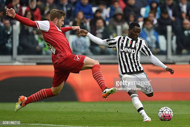 Kwadwo Asamoah of Juventus FC is challenged by Riccardo Gagliolo of Carpi FC during the Serie A match between Juventus FC and Carpi FC at Juventus...