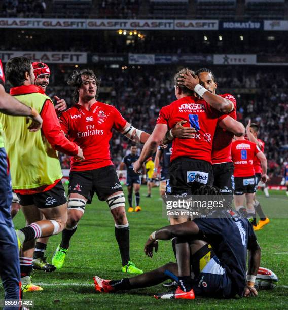 Kwagga Smith of the Lions celebrates with teammates after scoring a try during the Super Rugby match between Emirates Lions and Vodacom Bulls at...