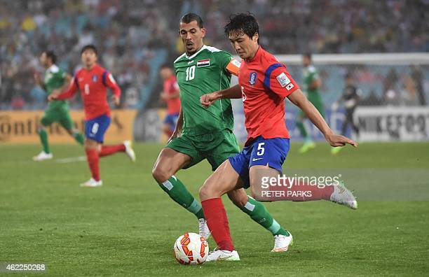 Kwak Taehwi of South Korea and Younus Mahmood of Iraq fight for the ball during the AFC Asian Cup semifinal football match in Sydney on January 26...