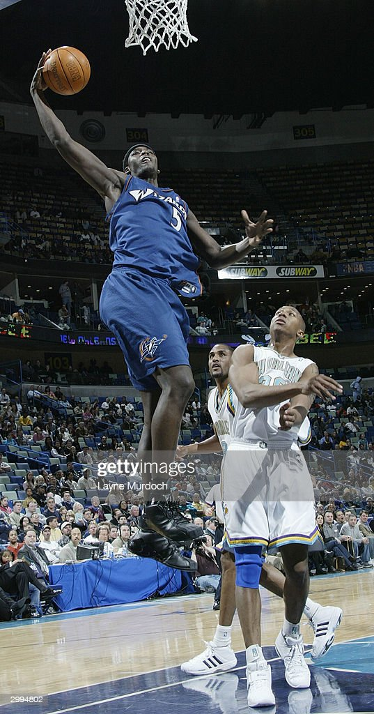 Kwame Brown of the Washington Wizards goes up for a dunk over David West of the New Orleans Hornets in NBA action February 18 2004 at the New Orleans...