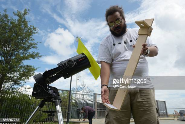 Kwayera Davis shows a solar eclipse viewer next to a telescope which he is seeing up in Charleston South Carolina on the day of the total solar...