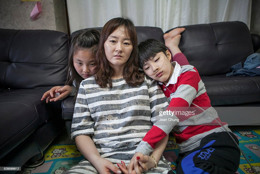 Kwon Mi-ae, (C) mother of Lim Seong-joon, 13, (R), who is suffering from chronic lung disease, and daughter, Lim Gyeong-min, 9, sit together at home on May 5, 2016 in Yongin, South Korea. His mother bought a humidifier sterilizer called 'Oxy Humidifier on Duty' back in 2003, and used the product with a humidifier for more than a year, subsequently damaging the lungs of Seong-joon. Seong-joon has gone through operations and now is living off of an oxygen tank 24 hours a day. His mother, Kwon Mi-ae, said that she thought of killing herself many times, but decided to live for him. Beginning in 2001, Reckitt Benckiser Korea (known as Oxy prior to 2014) used Polyhexamethylene guanidine (PHMG) in a humidifier sterilizer product called Oxy Ssak Ssak; the ingredient was dropped in 2011 when the Korea Centers for Disease Control and Prevention (KCDC) published a report showing a link between the compound and lung damage and deaths. Several companies in South Korea made humidifier sterliizers with poisonous ingredients between 2001 and 2011. According to a BBC report in May 2016, about 500 people, many of them women and children, are reported to have died or been injured after inhaling these ingredients. One of the victims's fathers is visiting U.K. right now, and a few other victims's families are planning to visit the U.K. at the end of May. The U.K.-based firm Reckitt Benckiser has admitted and apologized for selling a humidifier disinfectant that killed more than 100 people in South Korea on May 2, 2016.