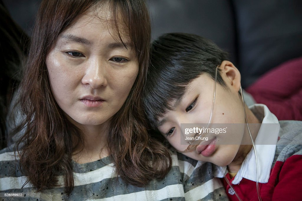 Kwon Mi-ae, (L) mother of Lim Seong-joon, 13, who is suffering from chronic lung disease, sits at home on May 6, 2016 in Yongin, South Korea. His mother bought a humidifier sterilizer called 'Oxy Humidifier on Duty' back in 2003, and used the product with a humidifier for more than a year, subsequently damaging the lungs of Seong-joon. Seong-joon has gone through operations and now is living off of an oxygen tank 24 hours a day. His mother, Kwon Mi-ae, said that she thought of killing herself many times, but decided to live for him. Beginning in 2001, Reckitt Benckiser Korea (known as Oxy prior to 2014) used Polyhexamethylene guanidine (PHMG) in a humidifier sterilizer product called Oxy Ssak Ssak; the ingredient was dropped in 2011 when the Korea Centers for Disease Control and Prevention (KCDC) published a report showing a link between the compound and lung damage and deaths. Several companies in South Korea made humidifier sterliizers with poisonous ingredients between 2001 and 2011. According to a BBC report in May 2016, about 500 people, many of them women and children, are reported to have died or been injured after inhaling these ingredients. One of the victims's fathers is visiting U.K. right now, and a few other victims's families are planning to visit the U.K. at the end of May. The U.K.-based firm Reckitt Benckiser has admitted and apologized for selling a humidifier disinfectant that killed more than 100 people in South Korea on May 2, 2016.