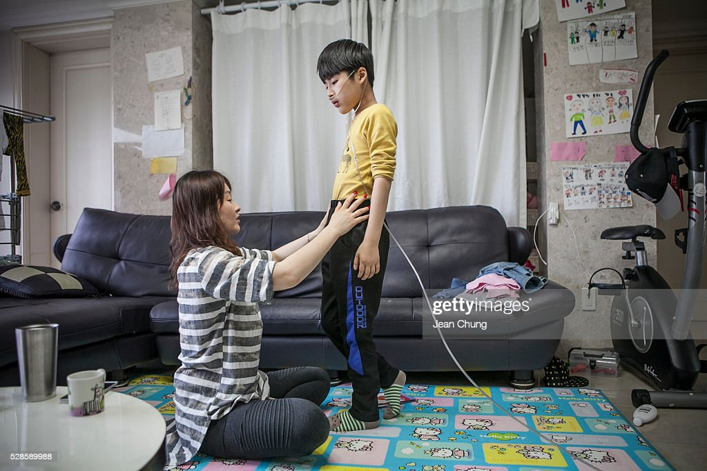 Kwon wn Mi-ae, mother of Lim Seong-joon, 13, who is suffering from chronic lung disease, dresses him in a pair of trousers as he is connected to an oxygen tank (not shown) at their home on May 6, 2016 in Yongin, South Korea. His mother bought a humidifier sterilizer called 'Oxy Humidifier on Duty' back in 2003, and used the product with a humidifier for more than a year, subsequently damaging the lungs of Seong-joon. Seong-joon has gone through operations and now is living off of an oxygen tank 24 hours a day. His mother, Kwon Mi-ae, said that she thought of killing herself many times, but decided to live for him. Beginning in 2001, Reckitt Benckiser Korea (known as Oxy prior to 2014) used Polyhexamethylene guanidine (PHMG) in a humidifier sterilizer product called Oxy Ssak Ssak; the ingredient was dropped in 2011 when the Korea Centers for Disease Control and Prevention (KCDC) published a report showing a link between the compound and lung damage and deaths. Several companies in South Korea made humidifier sterliizers with poisonous ingredients between 2001 and 2011. According to a BBC report in May 2016, about 500 people, many of them women and children, are reported to have died or been injured after inhaling these ingredients. One of the victims's fathers is visiting U.K. right now, and a few other victims's families are planning to visit the U.K. at the end of May. The U.K.-based firm Reckitt Benckiser has admitted and apologized for selling a humidifier disinfectant that killed more than 100 people in South Korea on May 2, 2016.