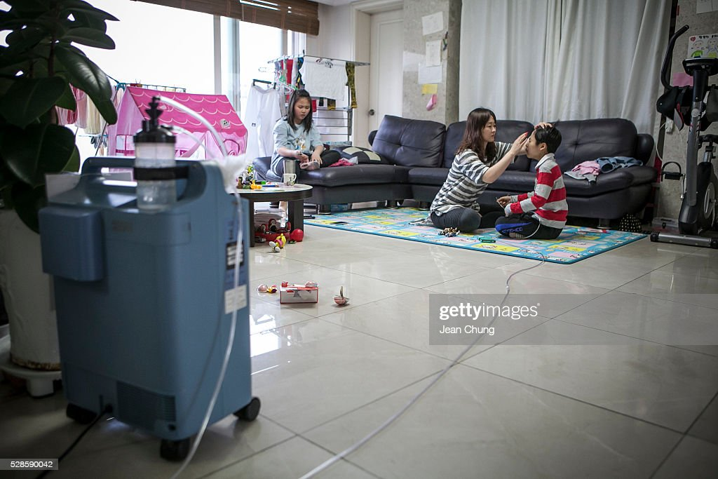 Kwon Mi-ae, (C) mother of Lim Seong-joon, 13, who is suffering from chronic lung disease, puts some cream on Seong-joon's face as he is connected with an oxygen tank, (L) at their home on May 6, 2016 in Yongin, South Korea. His mother bought a humidifier sterilizer called 'Oxy Humidifier on Duty' back in 2003, and used the product with a humidifier for more than a year, subsequently damaging the lungs of Seong-joon. Seong-joon has gone through operations and now is living off of an oxygen tank 24 hours a day. His mother, Kwon Mi-ae, said that she thought of killing herself many times, but decided to live for him. Beginning in 2001, Reckitt Benckiser Korea (known as Oxy prior to 2014) used Polyhexamethylene guanidine (PHMG) in a humidifier sterilizer product called Oxy Ssak Ssak; the ingredient was dropped in 2011 when the Korea Centers for Disease Control and Prevention (KCDC) published a report showing a link between the compound and lung damage and deaths. Several companies in South Korea made humidifier sterliizers with poisonous ingredients between 2001 and 2011. According to a BBC report in May 2016, about 500 people, many of them women and children, are reported to have died or been injured after inhaling these ingredients. One of the victims's fathers is visiting U.K. right now, and a few other victims's families are planning to visit the U.K. at the end of May. The U.K.-based firm Reckitt Benckiser has admitted and apologized for selling a humidifier disinfectant that killed more than 100 people in South Korea on May 2, 2016.