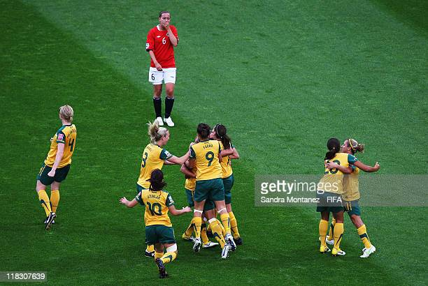 Kyah Simon of Australia celebrates with team mates after scoring her team's first goal while Kristine Wigdahl Hegland looks dejected during the FIFA...
