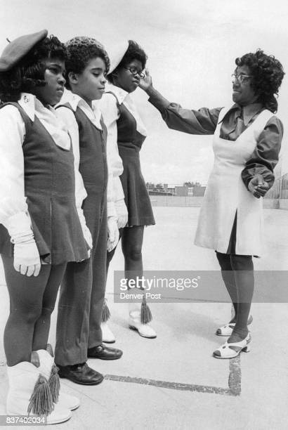 Kyla Cummings left Hugh Simien and Leslie Adams stand at attention as Mrs Beulah Adams organizer of the Escoolites inspects their drill uniforms...