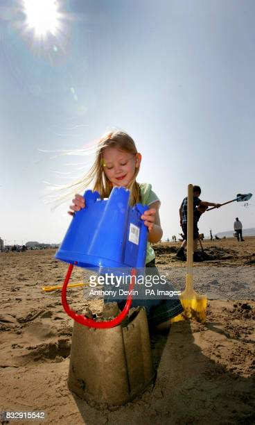 Kyla Garner builds a sandcastle on the beach in the holiday sunshine at WestonSuperMare Somerset