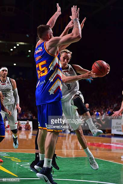 Kyle Adnam of Melbourne drives to the basket as Mitch Creek of the Adelaide 36ers defends during the round 15 NBL match between the Adelaide 36ers...