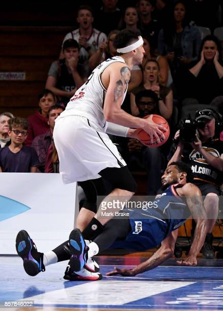 Kyle Adnam of Melbourne United knocks over Ramone Moore of the Adelaide 36ers for a charging foul during the round one NBL match between the Adelaide...