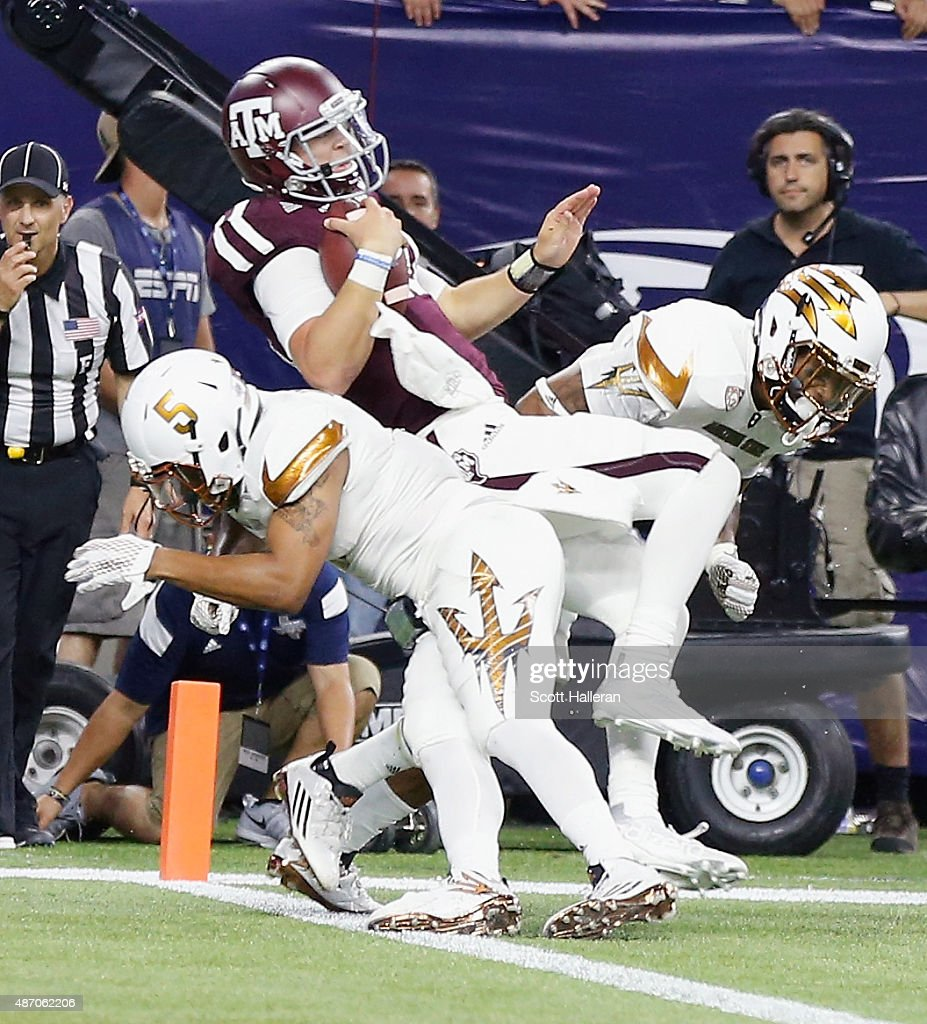 Kyle Allen of the Texas AM Aggies rolls over two Arizona State Sun Devils defenders for a touchdown in the second half during the Advocare Texas...