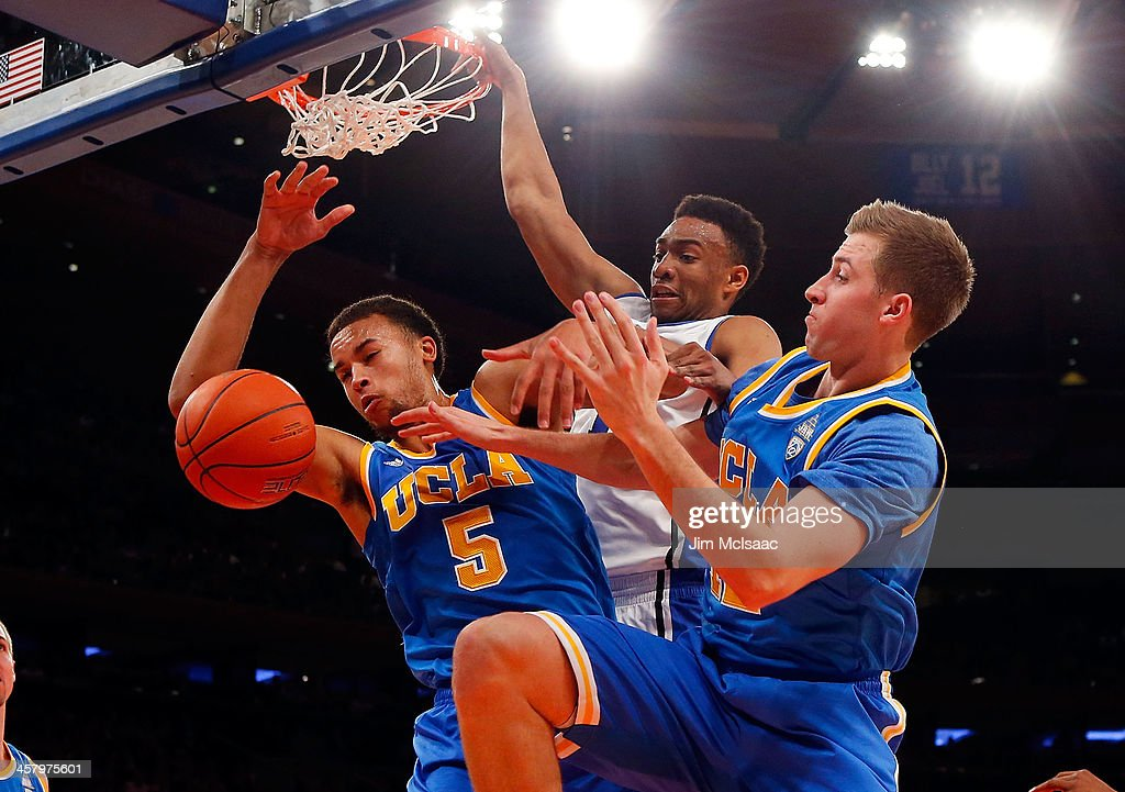 Kyle Anderson #5 and David Wear #12 of the UCLA Bruins battles for a rebound in the first half against Jabari Parker #1 of the Duke Blue Devils during the CARQUEST Auto Parts Classic on December 19, 2013 at Madison Square Garden in New York City.