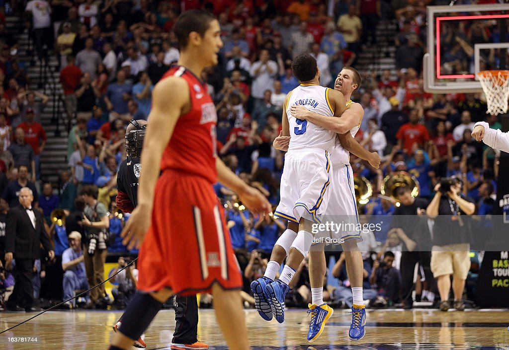 Kyle Anderson #5 and Travis Wear #24 of the UCLA Bruins celebrate as Nick Johnson #13 of the Arizona Wildcats walks by after the Bruins defeat the Wildcats 66-64 during the semifinals of the Pac-12 tournament at the MGM Grand Garden Arena on March 14, 2013 in Las Vegas, Nevada.