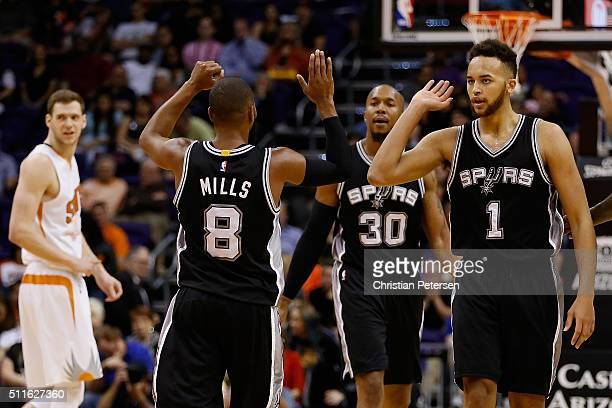 Kyle Anderson of the San Antonio Spurs celebrates with Patty Mills after scoring against the Phoenix Suns during the second half of the NBA game at...
