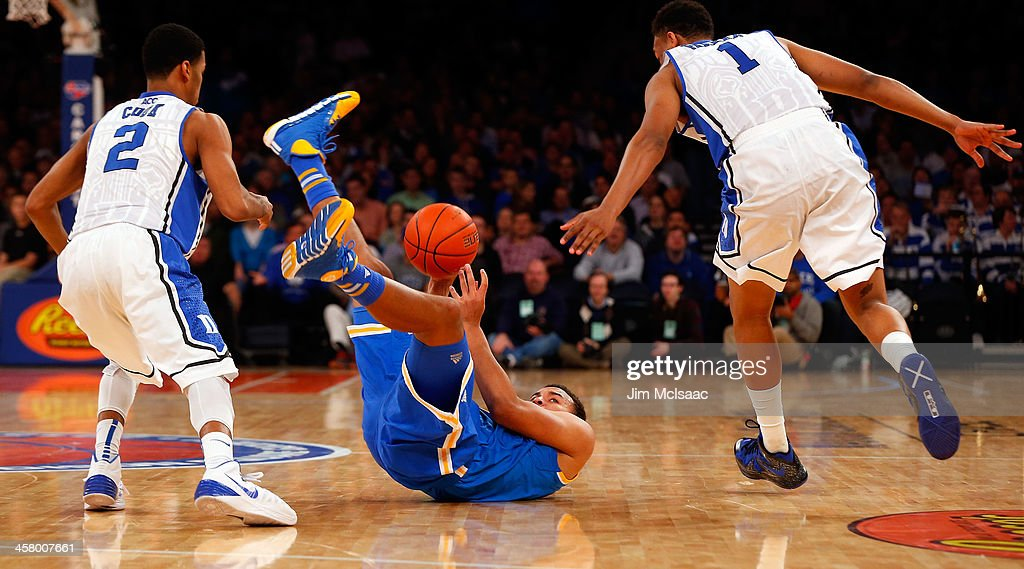 Kyle Anderson #5 of the UCLA Bruins loses the ball in the second half as he falls between Jabari Parker #1 and Quinn Cook #2 of the Duke Blue Devils during the CARQUEST Auto Parts Classic on December 19, 2013 at Madison Square Garden in New York City.