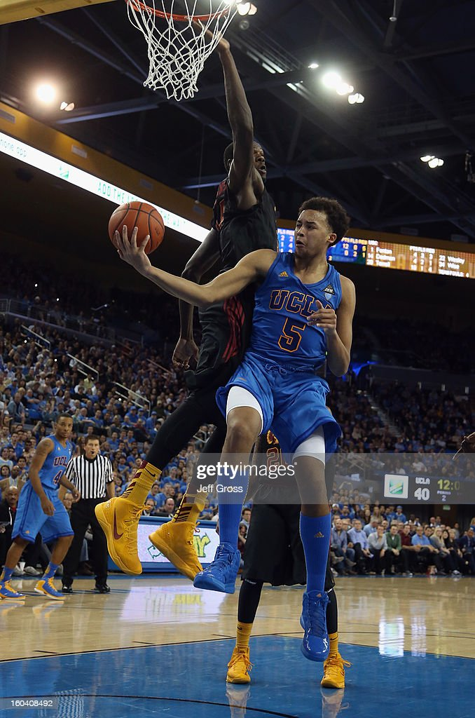 Kyle Anderson #5 of the UCLA Bruins passes the ball off while defended by Dewayne Dedmon #14 of the USC Trojans in the second half at Pauley Pavilion on January 30, 2013 in Los Angeles, California. USC defeated UCLA 75-71 in overtime.