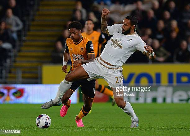 Kyle Bartley of Swansea City tackles Chuba Akpom of Hull City during the Capital One Cup third round match between Hull City and Swansea City at KC...