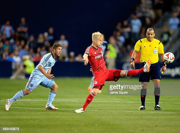 Kyle Bekker of Toronto FC lunges for the ball as Alex Martinez of Sporting KC defends during the game at Sporting Park on May 23 2014 in Kansas City...
