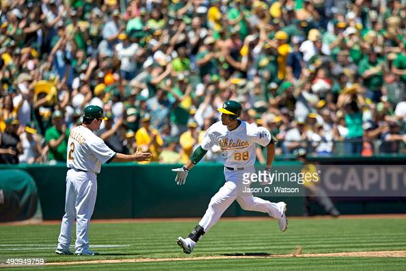 Kyle Blanks of the Oakland Athletics is congratulated by third base coach Mike Gallego after hitting a home run off of Drew Smyly of the Detroit...