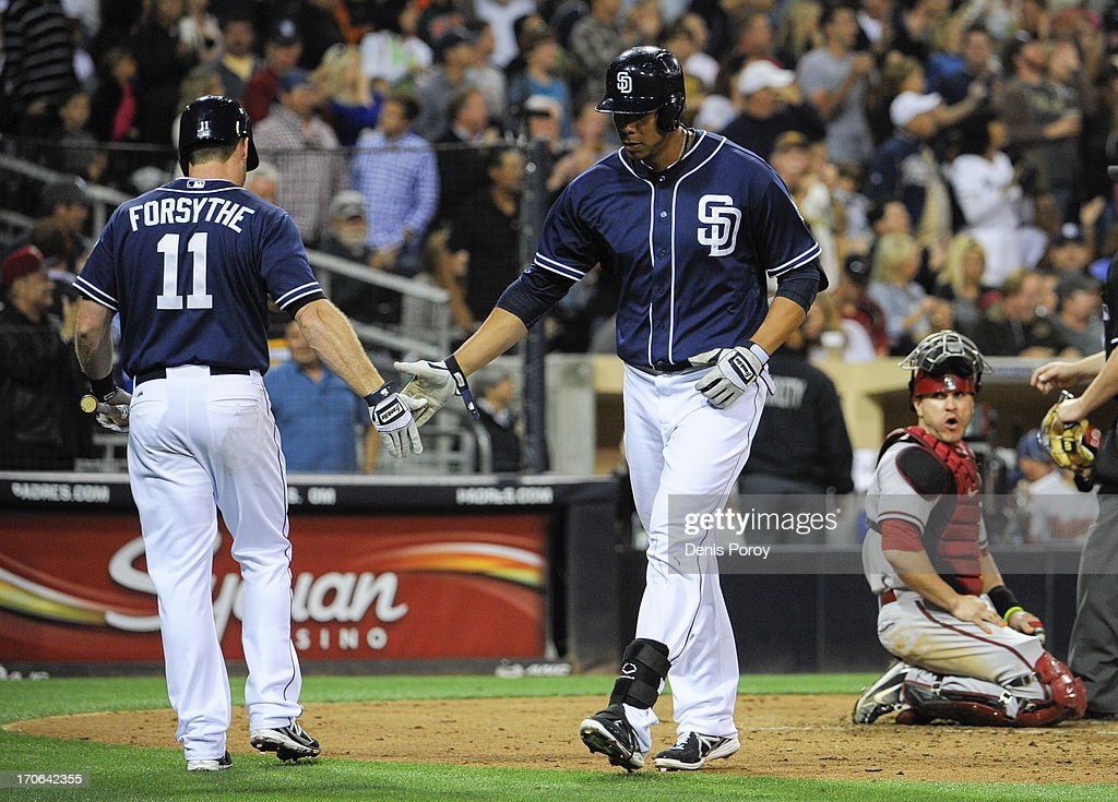 Kyle Blanks #88 of the San Diego Padres, center, is congratulated by Logan Forsythe #11 after hitting a solo home as Miguel Montero #26 of the Arizona Diamondbacks, right, looks on during the sixth inning of a baseball game at Petco Park on June 15, 2013 in San Diego, California.