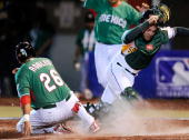Kyle Botha of South Africa looks for the ball as Oscar Robles of Mexico scores a run on an errant throw from first baseman Brett Willemburg during...