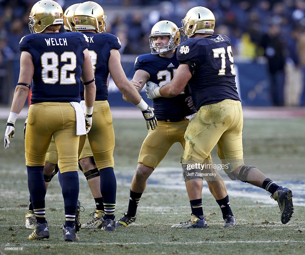 Kyle Brindza #27 celebrates with Steve Elmer #79 of the Notre Dame Fighting Irish during the New Era Pinstripe Bowl against the Rutgers Scarlet Knights at Yankee Stadium on December 28, 2013 in the Bronx borough of New York City.