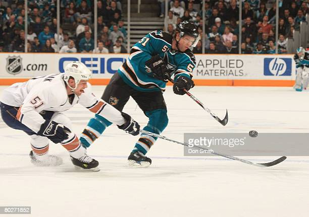 Kyle Brodziak of the Edmonton Oilers reaches across Brian Campbell of the San Jose Sharks during a NHL game on March 16 2008 at HP Pavilion at San...