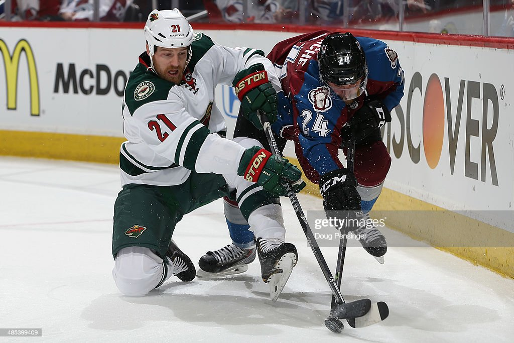 Kyle Brodziak of the Minnesota Wild and MarcAndre Cliche of the Colorado Avalanche battle for control of the puck in Game One of the First Round of...