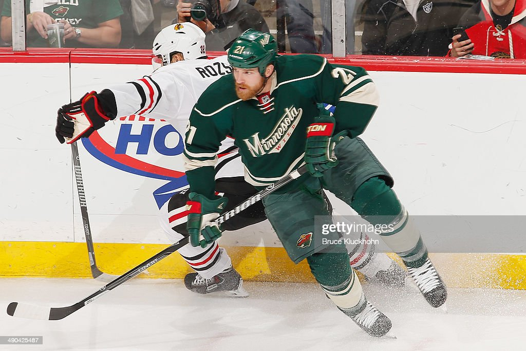 Kyle Brodziak of the Minnesota Wild and Michal Rozsival of the Chicago Blackhawks skate to the puck during Game Four of the Second Round of the 2014...
