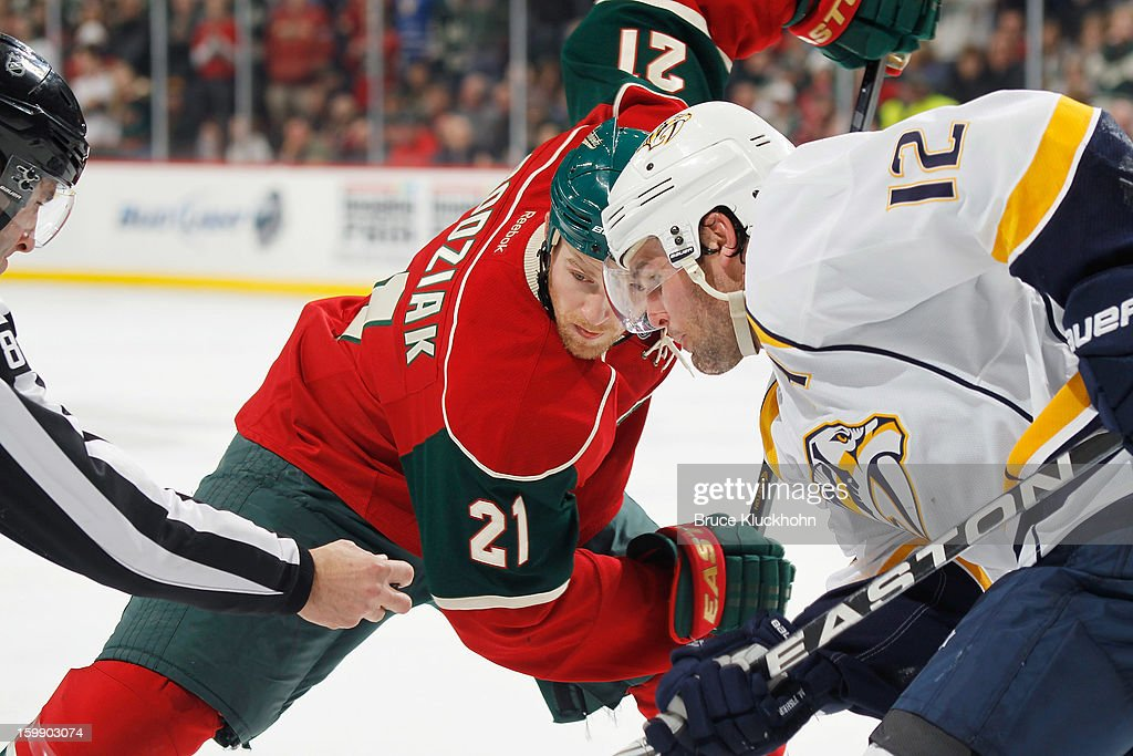 Kyle Brodziak #21 of the Minnesota Wild and Mike Fisher #12 of the Nashville Predators face-off during the game on January 22, 2013 at the Xcel Energy Center in Saint Paul, Minnesota.