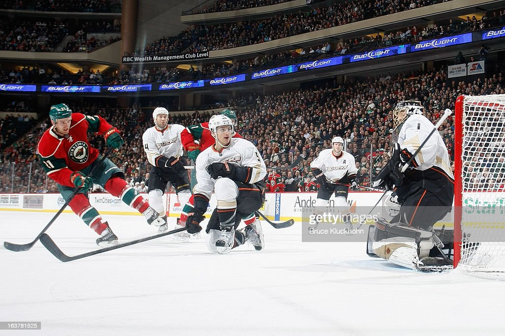 Kyle Brodziak #21 of the Minnesota Wild attempts to score with Luca Sbisa #5 and goalie Jonas Hiller #1 of the Anaheim Ducks defending during the game on March 12, 2013 at the Xcel Energy Center in Saint Paul, Minnesota.