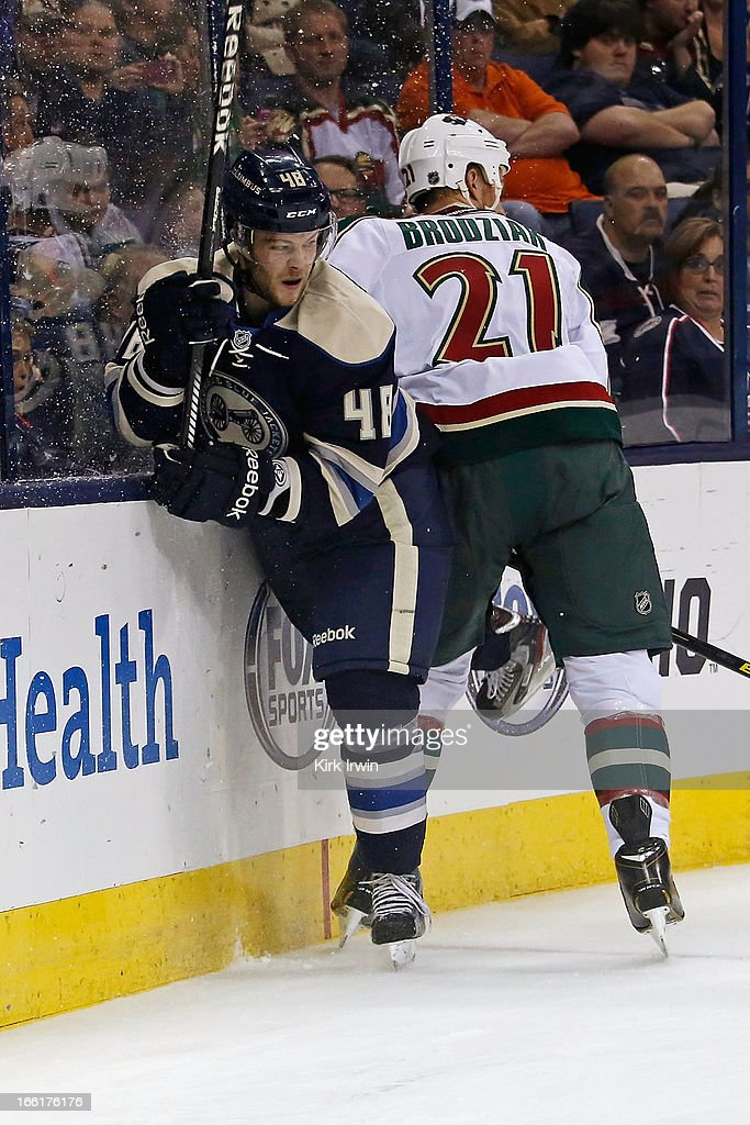 Kyle Brodziak #21 of the Minnesota Wild checks Cody Goloubef #48 of the Columbus Blue Jackets while chasing after a loose puck on April 7, 2013 at Nationwide Arena in Columbus, Ohio.