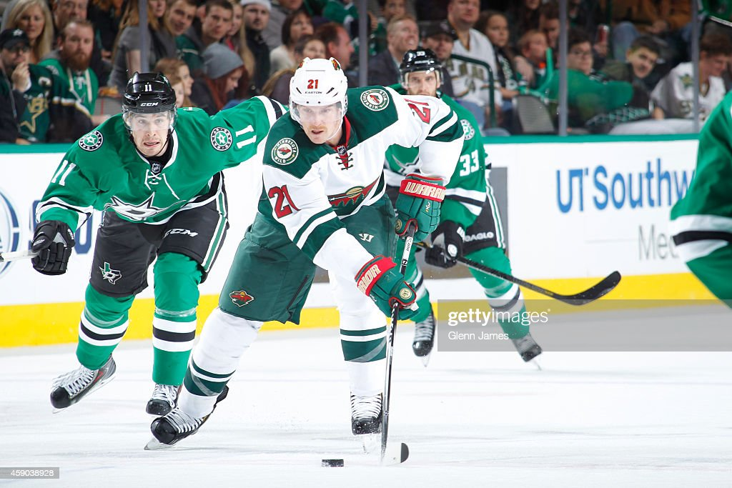 Kyle Brodziak of the Minnesota Wild handles the puck against Curtis McKenzie of the Dallas Stars at the American Airlines Center on November 15 2014...