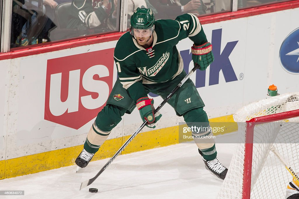 Kyle Brodziak of the Minnesota Wild handles the puck against the Boston Bruins during the game on December 17 2014 at the Xcel Energy Center in St...
