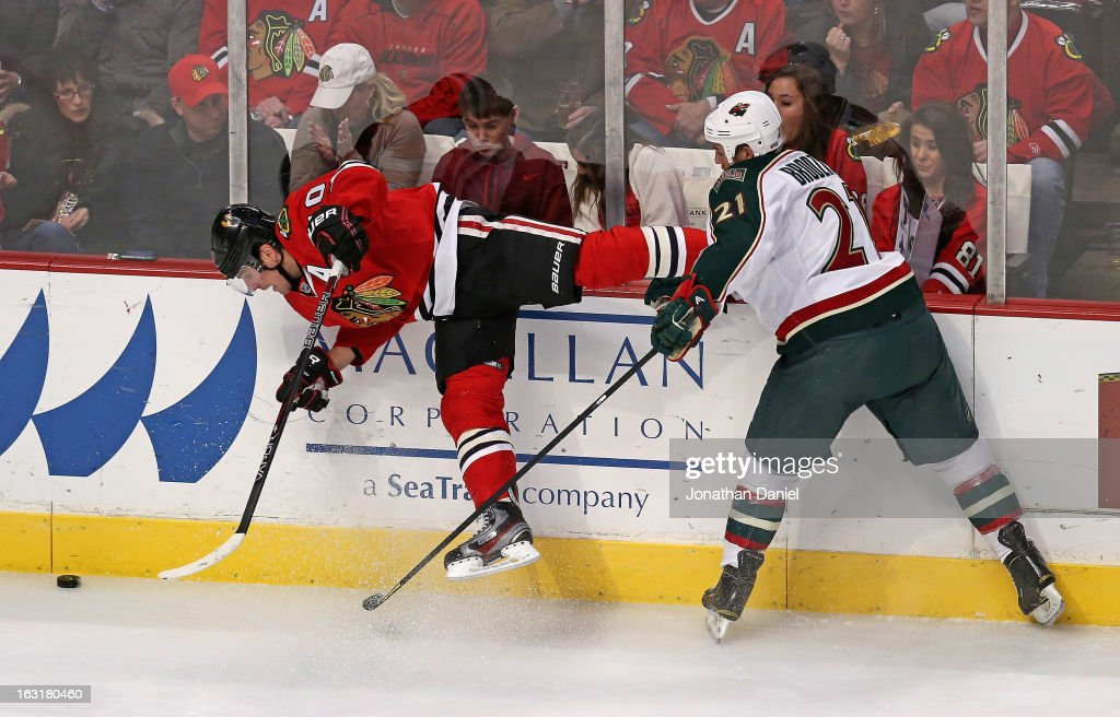 Kyle Brodziak #21 of the Minnesota Wild hits Patrick Sharp #10 of the Chicago Blackhawks forcing him off of his feet at the United Center on March 5, 2013 in Chicago, Illinois.