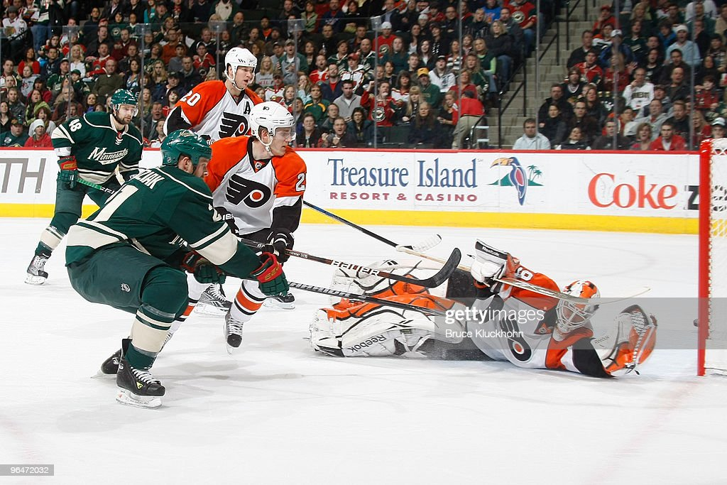 Kyle Brodziak of the Minnesota Wild narrowly misses the net after shooting the puck past goalie Michael Leighton of the Philadelphia Flyers during...