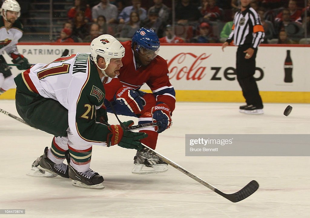 Kyle Brodziak of the Minnesota Wild shoots the puck as PK Subban of the Montreal Canadiens checks him at the Bell Centre on September 26 2010 in...