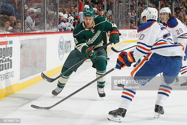Kyle Brodziak of the Minnesota Wild skates to the puck with Eric Belanger of the Edmonton Oilers defending during the game on April 26 2013 at the...