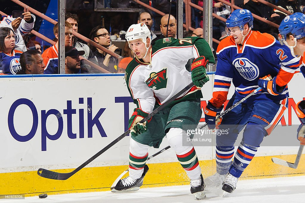 Kyle Brodziak #21 of the Minnesota Wild skates with the puck against Jeff Petry #2 of the Edmonton Oilers during an NHL game at Rexall Place on February 21, 2013 in Edmonton, Alberta, Canada.