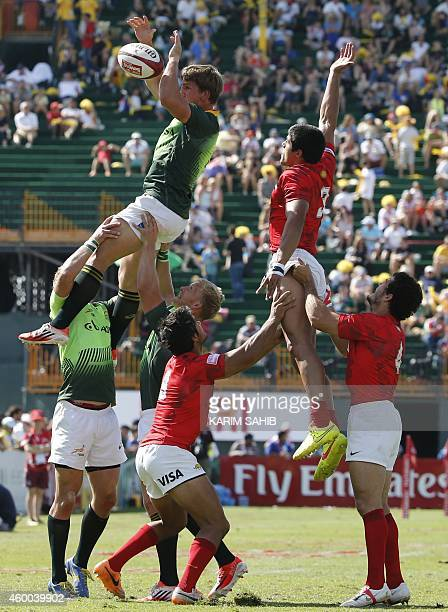Kyle Brown of South Africa and Axel Muller of Argentina are lifted by their teammates in a lineup during their quarterfinal rugby match in the Dubai...
