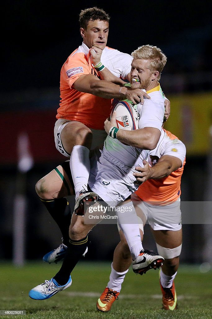 Kyle Brown #6 of South Africa is tackled by Juan Cappiello #8 of Argentina during the Tokyo Sevens, in the six round of the HSBC Sevens World Series at the Prince Chichibu Memorial Ground on March 22, 2014 in Tokyo, Japan.
